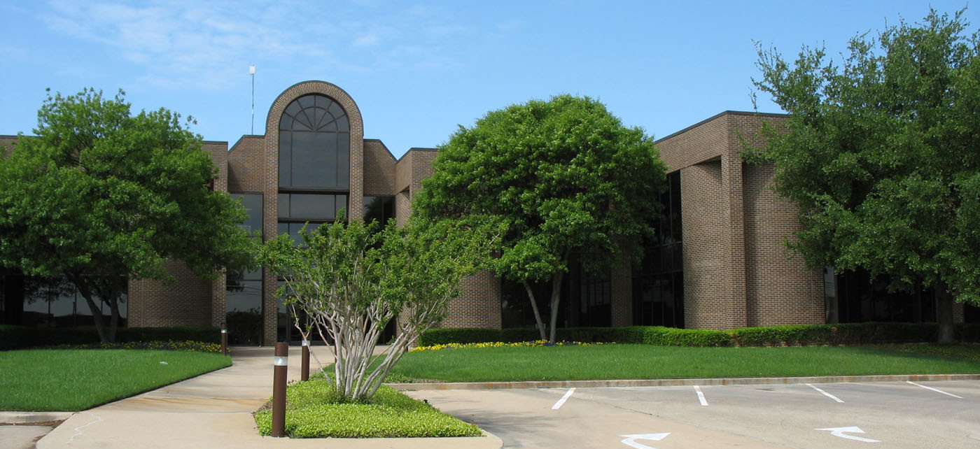 Office complex with lush green lawn and plants in Hurst, Texas