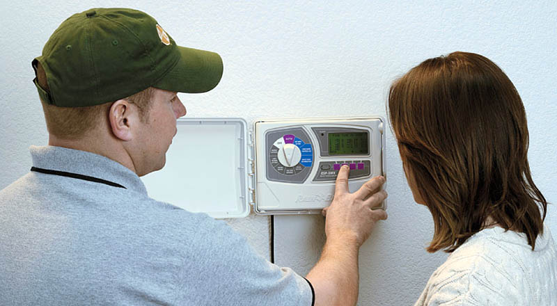 sprinkler repair and installation specialist shows customer how to program her timer